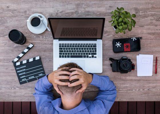 Usuario frustrado con las manos en la cabeza, sentado delante del portatil